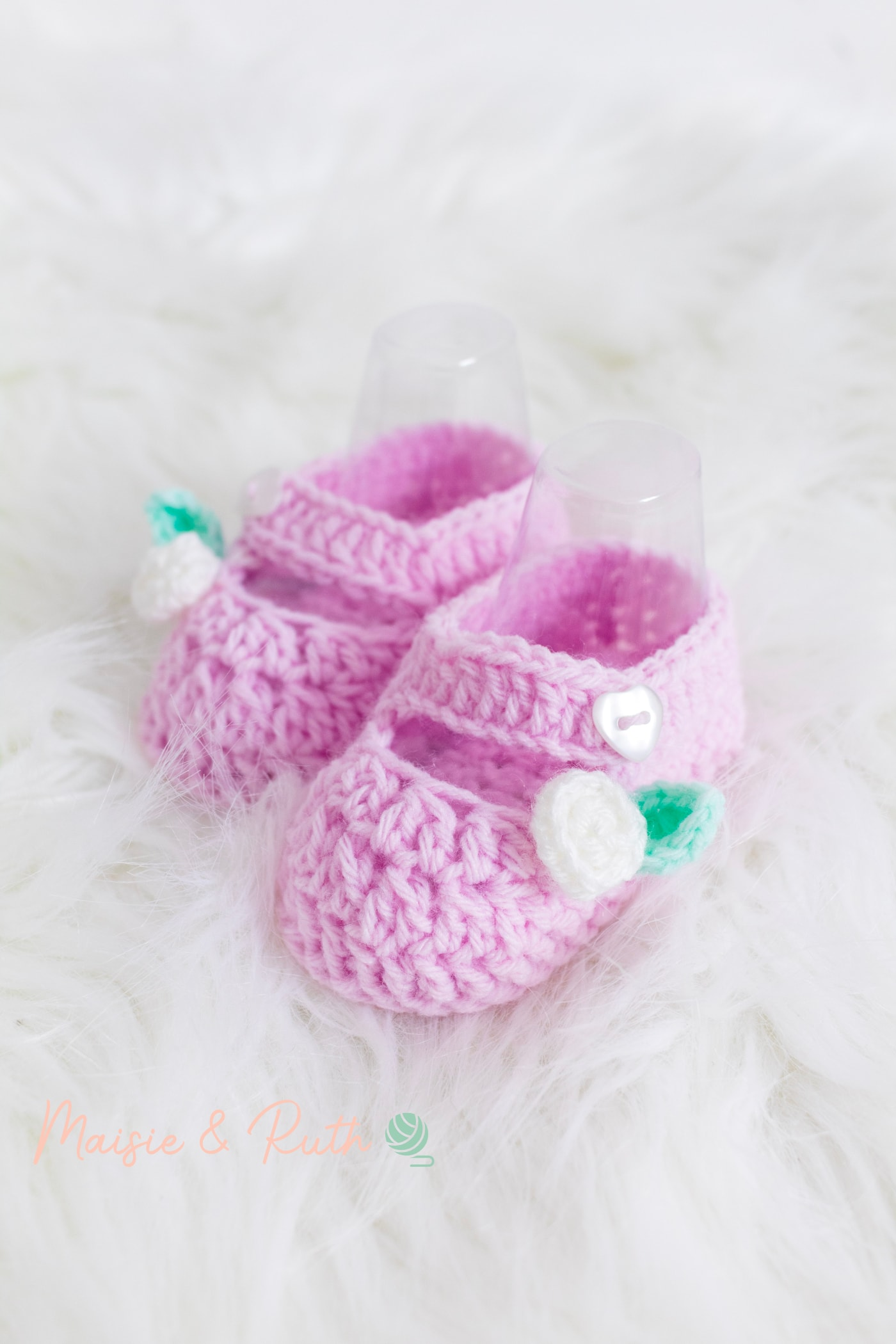 Crochet Baby Booties Pattern Pink Shoe on fluffy rug